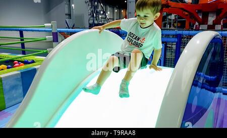Image de 3 ans Bébé garçon à cheval sur la diapositive sur l'aire de jeux au centre commercial Banque D'Images