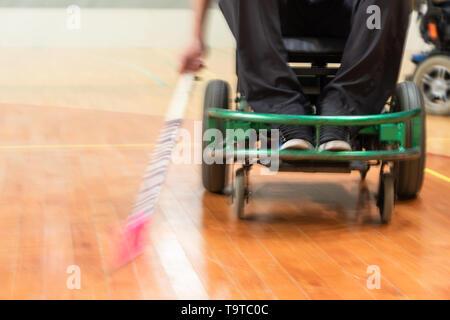 Homme handicapé sur un fauteuil roulant électrique jouant des sports, hockey powerchair. IWAS - fauteuil roulant International iwbf et