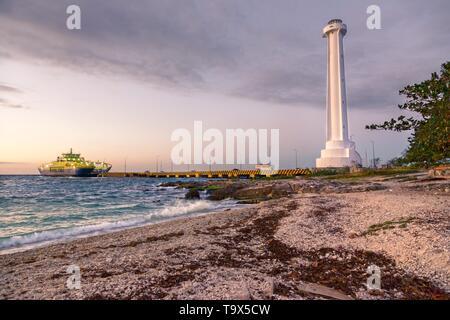 Ciel Coucher de soleil spectaculaire couleurs avec le Caribbean Beach et phare de voiture Ferry Pier à Cozumel, Mexique Yucatan