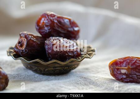Dattes séchées dans un bol de fruits sur lin, Close up. Banque D'Images