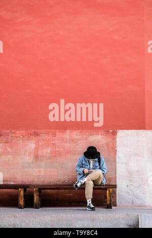 Une femme assise sur le banc en face du grand mur rouge de la Cité interdite à Pékin, Chine Banque D'Images