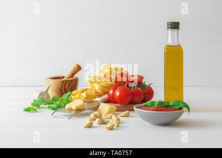 Table avec des ingrédients pour faire des tomates séchées. Tomates, ail, basilic et origan frais herbes, bouteille d'huile d'olive, quelques noix de cajou, fromage parmesan, c Banque D'Images