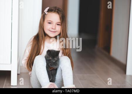 Smiling girl enfant 4-5 ans holding petit chaton assis sur le plancher dans la chambre. En regardant la caméra. L'enfance. Banque D'Images