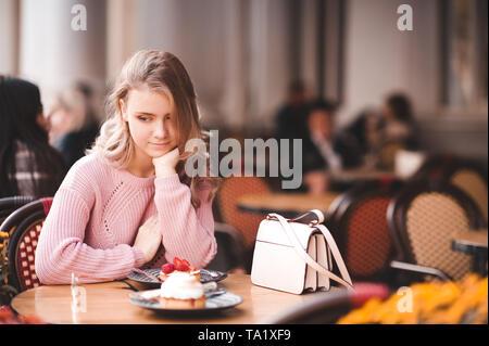 Teen blonde Fille 16-17 ans assis dans cafe manger un gâteau à l'extérieur. La saison d'été. Banque D'Images
