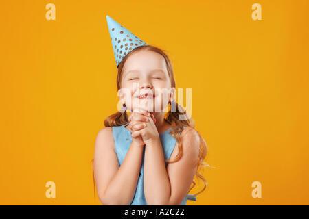 Cute little girl célèbre l'anniversaire. L'enfant ferma les yeux et fait un vœu. Closeup portrait sur fond jaune. Banque D'Images