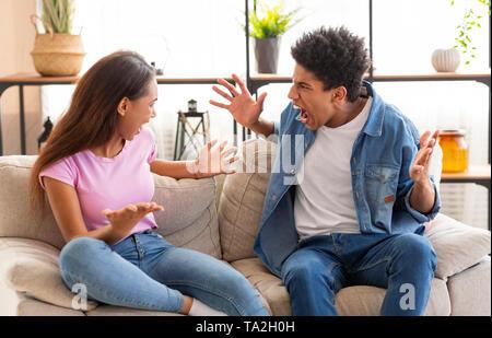 Les adolescents au garçon et fille se quereller, gesticulant et criant à l'autre Banque D'Images