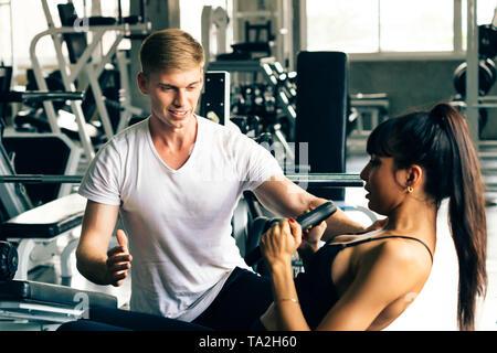 Jeune homme de race blanche entraîneur personnel en chemise blanche dans une salle de sport, d'aider et de soutenir les clients de remise en forme féminine. Elle fait abdominaux. Banque D'Images