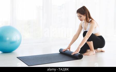 Jeune femme yoga mat son matériel roulant après la formation Banque D'Images