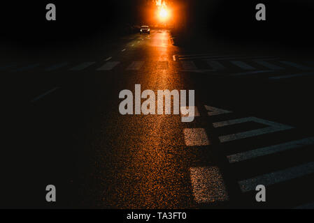 Contexte urbain d'une rue sombre au crépuscule avec des voitures et des marques de circulation Banque D'Images
