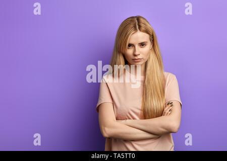 Jeune femme blonde grincheuse en colère en beige T-shirt en gardant les bras pliés, looking at camera avec de strictes et sceptique à l'expression. copie espace confiance.co Banque D'Images