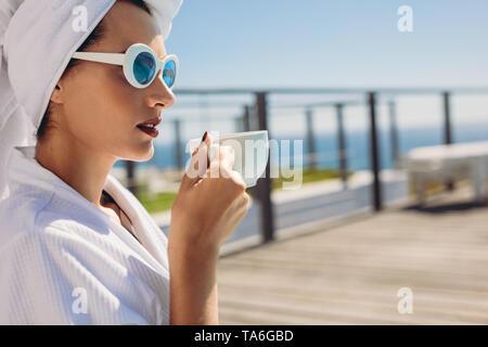 Belle femme assise par le café de la piscine. Modèle féminin wearing bathrobe et lunettes de se détendre au bord de l'eau. Banque D'Images