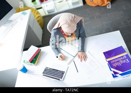 Vue de dessus du professeur de français à porter le hijab à la table de travail Banque D'Images