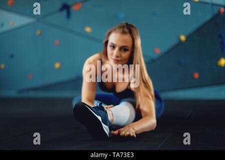Gymnaste girl doing Stretching Exercices de réchauffement. Voir de jeunes femme sports au gym crossfit