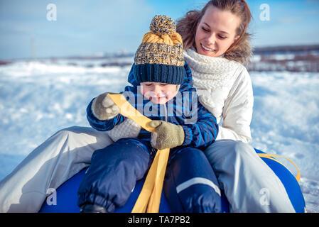 Une jeune mère, femme avec enfant, garçon, fils de 3 ans, dans l'hiver à l'extérieur dans des vêtements chauds, assis sur un tube, dévalant une colline, jouer
