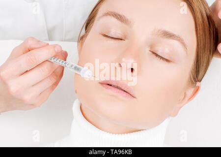 Belle femme qui reçoit l'injection de remplissage dans les lèvres. Traitement anti-vieillissement et l'ascenseur de visage. Traitement cosmétique. Levage de la peau du visage de femme à injection f