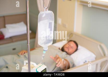 Close-up. Côté masculin avec un compte-gouttes pendant la chimiothérapie dans un hôpital. L'homme est dans la chambre d'hôpital, sans accent. La santé est un sujet de la santé et Banque D'Images