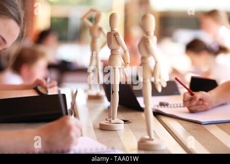 Les élèves de l'extérieur de l'école secondaire en bois dessin mannequins d'art visuel. leçon de classe et de formation des artistes d'attirer l'apprentissage figure humaine études.. Banque D'Images
