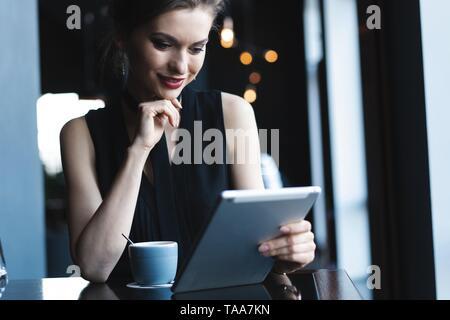Young attractive woman sitting in coffee shop pendant le temps libre et de travail sur l'ordinateur tablette. Heureux d'avoir des femmes reste dans le café. Style de vie. Banque D'Images