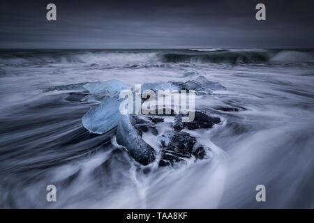 Dérives dans la mer autour de l'icebergs et de la glace des glaciers qui est balayée sur la plage sur le sable noir à Jokulsarlon, Islande Banque D'Images