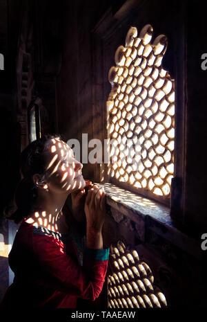 Femme en rouge sur le balcon du Penjab indien près de la fenêtre dans le musée du palais de la ville d'Udaipur, Rajasthan, Inde Banque D'Images