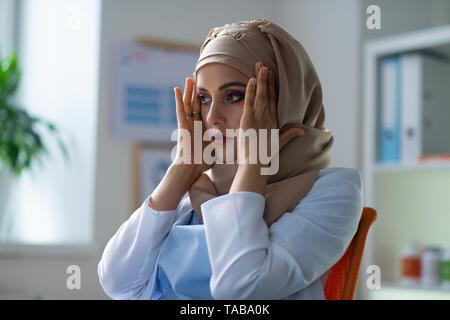 Pharmacie de hijab. Belle chimiste aux yeux noirs portant le hijab et l'uniforme blanc de malaise Banque D'Images