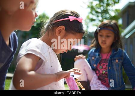 Belle image en couleur d'un jeune preteen Asian Girls entouré d'amis et de la famille célébrant son anniversaire dans un parc et déballer présente Banque D'Images