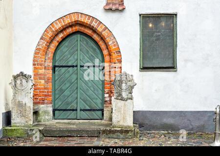 Porte en bois ancien de couleur verte avec un arc d'une brique rouge sur fond d'un mur de couleur bleu pâle. À partir de la série de porte du monde. Banque D'Images