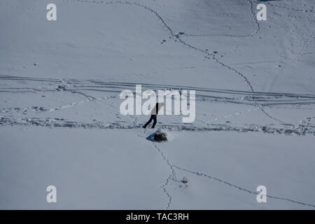 Un homme marchant lourdement par des routes verglacées dans le Lonely planet de la neige à Kibber, village de la vallée de Spiti, Inde - vie de village de Kibber Banque D'Images