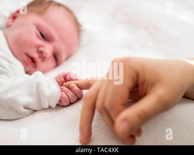Newborn girl holding mères doigt Banque D'Images