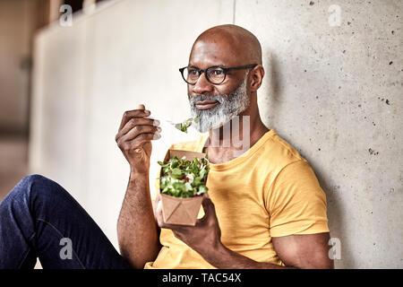 Mature businessman having lunch break de manger une salade Banque D'Images