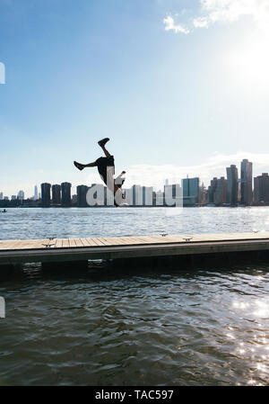 USA, New York, Brooklyn, jeune homme faisant backflip sur la jetée en face de Manhattan skyline