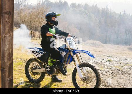 Pilote de motocross sur moto avec de la fumée sortir du tuyau d'échappement Banque D'Images