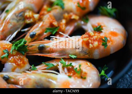 Fruits de mer crevettes Crevettes avec dîner gastronomique, fruits de mer cuits avec la sauce d'herbes et d'épices sur fond pan / Close up les crustacés crevettes cuites
