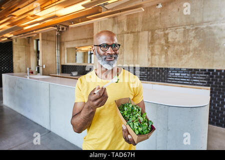 Mature businessman having a salad in modern office Banque D'Images
