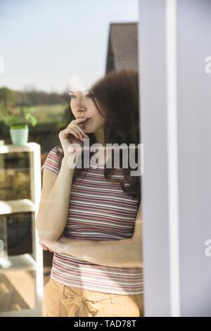 Portrait de jeune femme pensive derrière la vitre