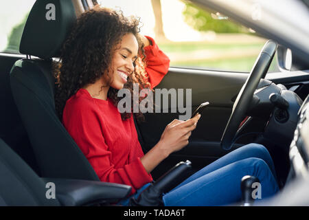 Smiling young woman using cell phone in a car