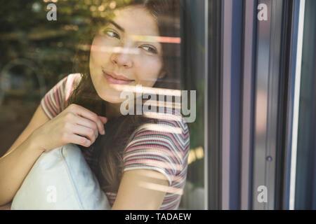 Portrait de jeune femme derrière la vitre