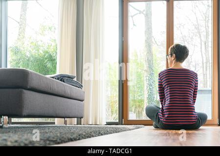 Vue arrière de femme assise sur le plancher de salle de séjour à la fenêtre de