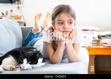 Portrait of little girl lying on couch with cat