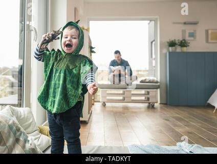 Happy boy dans un costume Playing with toy figure à la maison Banque D'Images
