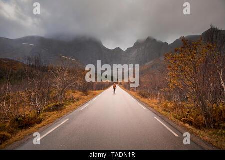 La Norvège, îles Lofoten, l'homme debout sur la route vide entourée de rock face Banque D'Images