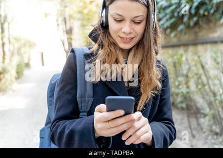 Jeune femme avec l'aide d'écouteurs, smartphone, marcher dans la ville