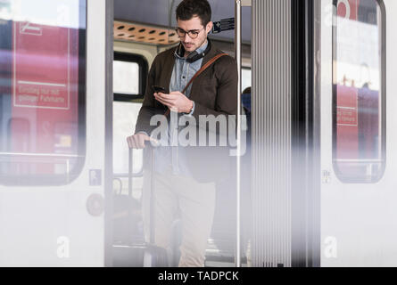 Young man using cell phone in commuter train Banque D'Images