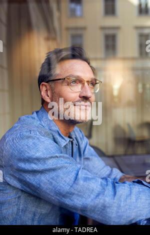 Portrait d'un homme portant des lunettes derrière la vitre Banque D'Images
