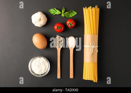 Mise à plat avec des pâtes composition ingrédients sur fond noir, de l'espace pour le texte
