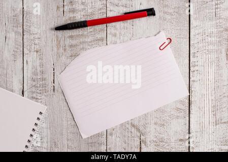 Papier déchiré et feuille de bloc-notes avec un stylo placé sur le dessus de table en bois. Banque D'Images