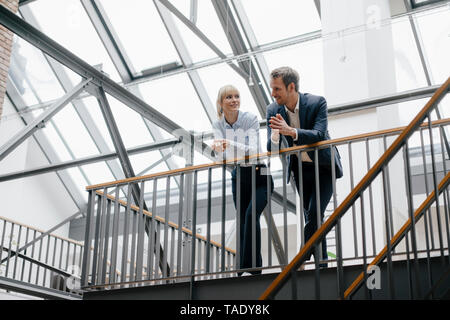 Man and Woman standing in office building, discuter Banque D'Images
