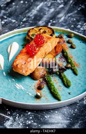 Tranche de saumon grillé garni d'asperges vertes cuites, tomates cerise et citron au cari Banque D'Images