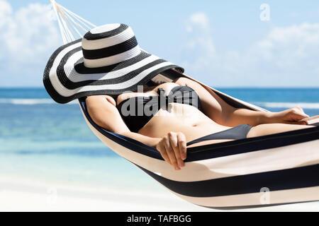 Young Woman in Bikini dormir sur hamac avec chapeau rayé à plage idyllique Banque D'Images