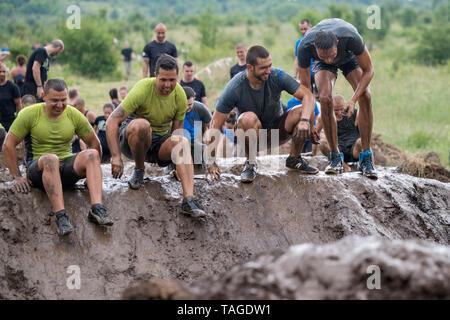 SOFIA, BULGARIE - le 7 juillet 2018: une équipe d'hommes sautant dans un sondage de boue pour surmonter les obstacles à un dosage de la boue race Banque D'Images